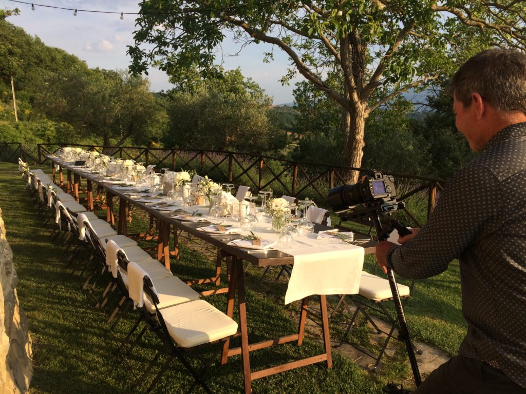 Filmmaker capturing wedding table at sunset